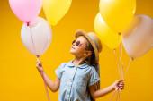 boldog gyerek szalmakalapban és napszemüvegben nézi a lufikat elszigetelt sárga