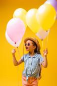 užaslé dítě v slamáku a slunečních brýlích drží balónky izolované na žluté