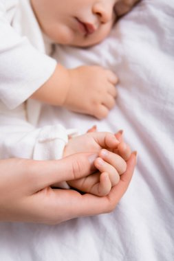 Woman touching hand of little son sleeping on white bedding, blurred background stock vector