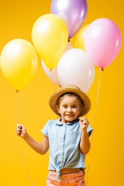 Happy kid in straw hat holding balloons isolated on yellow stock vector