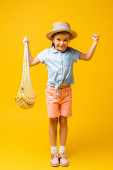 full length of excited child in straw hat holding reusable string bag with bananas on yellow