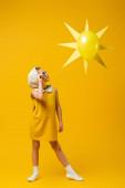 teljes hossza lány fejkendő és napszemüveg nézi dekoratív nap léggömb sárga