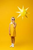 Nachdenkliches Mädchen mit Kopftuch und Sonnenbrille steht neben dekorativer Sonne mit Luftballon auf gelb