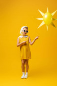 in voller Länge glückliches Mädchen mit Kopftuch und Sonnenbrille, das mit den Fingern auf dekorative Sonne mit Luftballon auf gelb zeigt