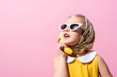 lány fejkendőt és napszemüveget tartó banán közel fül elszigetelt rózsaszín