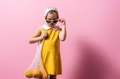 dívka v šátku nastavení sluneční brýle při držení opakovaně použitelný provázek taška s pomeranči na růžové
