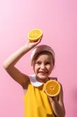 usmívající se dívka v šátku drží oranžové půlky na růžové