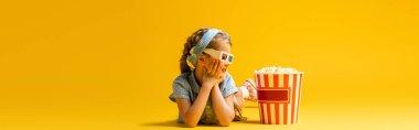 Happy kid in 3d glasses lying near popcorn bucket on yellow, banner stock vector