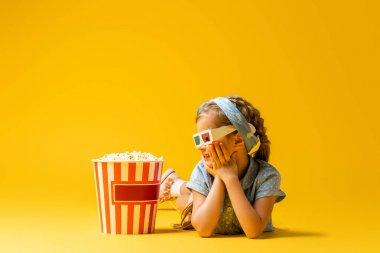 Happy kid in 3d glasses lying and looking at popcorn bucket on yellow stock vector
