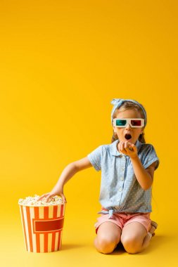 amazed kid in 3d glasses eating popcorn and reaching bucket on yellow