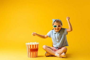 Happy kid in 3d glasses sitting with crossed legs near popcorn bucket on yellow stock vector