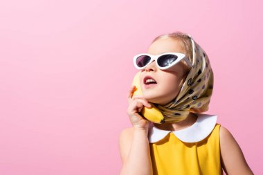 Girl in headscarf and sunglasses holding banana near ear isolated on pink stock vector