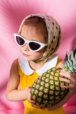 Kid in headscarf and sunglasses holding pineapple on pink stock vector