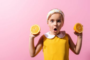 Shocked girl in headscarf holding orange halves isolated on pink stock vector