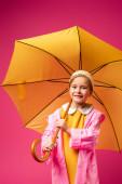 potěšená dívka v pláštěnce, stojící pod deštníkem izolovaná na karmínovém
