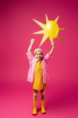 plná délka šťastné dívky v pláštěnce a gumové boty drží dekorativní slunce s balónem na karmínu