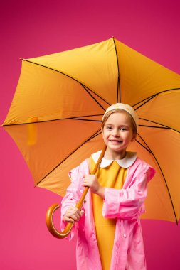 Pleased girl in raincoat standing under umbrella isolated on crimson stock vector