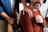 Teilbild eines Mannes, der Schulter eines lebenslustigen behinderten Vaters berührt