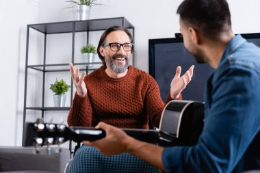 excited disabled man showing wow gesture near son playing guitar on blurred foreground