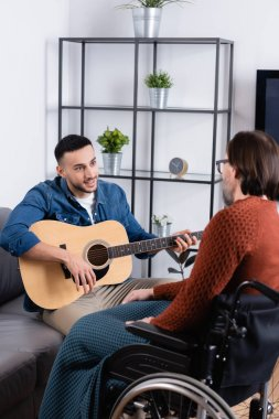 young hispanic man playing guitar near disabled father on blurred foreground