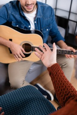 cropped view of handicapped man pointing with hand near son playing guitar on blurred background