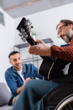 low angle view of handicapped man playing guitar near hispanic son on blurred background