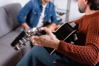 partial view of disabled man playing acoustic guitar near son on blurred background