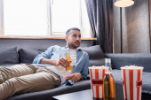 young hispanic man drinking beer and watching tv while lying on sofa