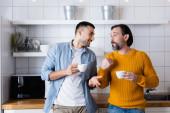 interracial otec a syn drží šálek kávy a gesta při rozhovoru v kuchyni