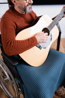 cropped view of smiling disabled man playing acoustic guitar in wheelchair