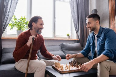 Happy interracial father and son looking at each other while playing chess at home stock vector