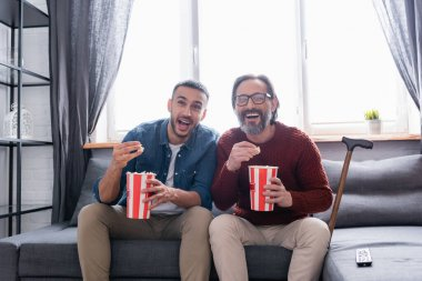 Excited interracial father and son laughing while watching comedy and eating popcorn at home stock vector