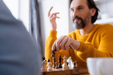 Selective focus of bearded man gesturing while playing chess on blurred foreground stock vector