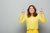 smiling woman in yellow shirt holding crossed fingers while looking up on grey
