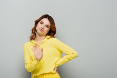 displeased woman showing refuse gesture while standing with hand on hip on grey