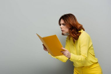 Shocked woman in yellow blouse staring at notebook on grey stock vector