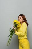 potěšená žena drží žluté chryzantémy, zatímco stojí se zavřenýma očima na šedé