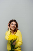 radostná žena opravuje kudrnaté vlasy a dívá se stranou, zatímco drží žluté květy na šedé