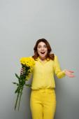 užaslá žena drží žluté květy, zatímco stojí s otevřenými ústy na šedé