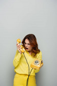 angry woman screaming while holding vintage phone on grey