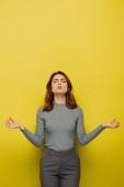 žena s kudrnatými vlasy a zavřenýma očima nadýmající tváře při meditaci na žlutou