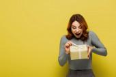 užaslá mladá žena tahání stuhu na dárek na žluté