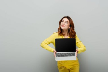 Smiling woman looking away while holding laptop with blank screen on grey stock vector