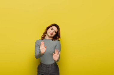 dissatisfied woman looking at camera while showing stop gesture on yellow