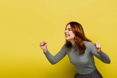 Amazed woman with wavy hair and clenched fists on yellow stock vector