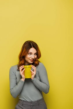Joyful young woman with curly hair holding paper cup and looking away on yellow stock vector