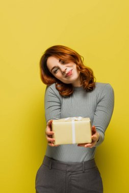 Happy young woman holding gift box and smiling on yellow stock vector