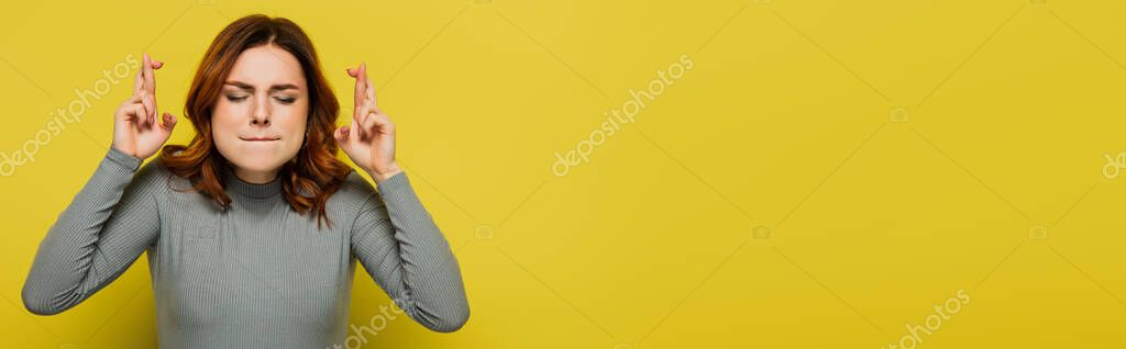 Tense woman with crossed fingers standing with closed eyes on yellow, banner stock vector