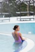 mladá žena v plavkách dívá pryč v venkovní bazén