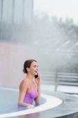 šťastná žena v plavkách mluvit na smartphone při smíchu a koupání ve venkovním bazénu